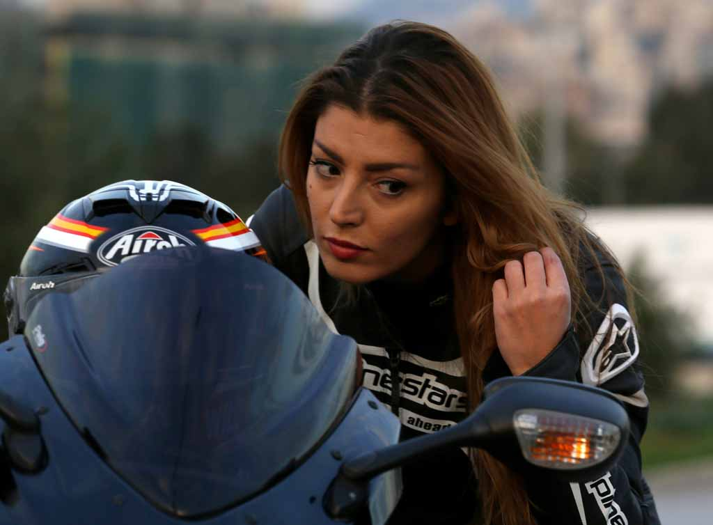"""Lebanese race biker Annie Bader fixes her hair on her motorbike in Dbayeh north of the Lebanese capital Beirut, on December 12, 2015. Bader, who is a Human Ressources manager, is also the first Arab woman to ever participate in International Motorcycle races in 2013 and 2014 as she took part in the Qatar Superbike Championship 600cc division to represent Lebanon and female Arabs. Bader was passionate about motorcycles ever since she was a little girl but said she never thought she would actually do something about her passion since the """"Lebanese society doesn't encourage women to practice such manly hobbies"""". AFP PHOTO / PATRICK BAZ / AFP / PATRICK BAZ"""