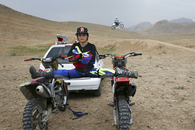 Iranian motocross rider Behnaz Shafiei poses for a photo as she stretches her legs